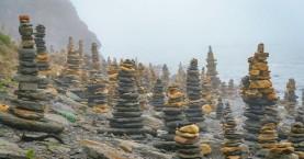Παραλία γεμάτη με πύργους από πέτρες
